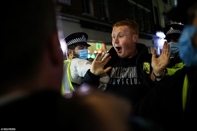 A man appeared to shout as he was grabbed by two police officers and taken away during an outburst in Soho, London