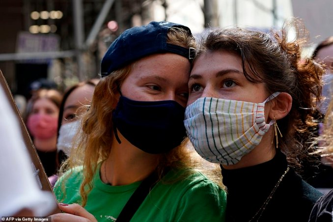Masked demonstrators watch and listen to a speaker during a protest in New York City on Saturday