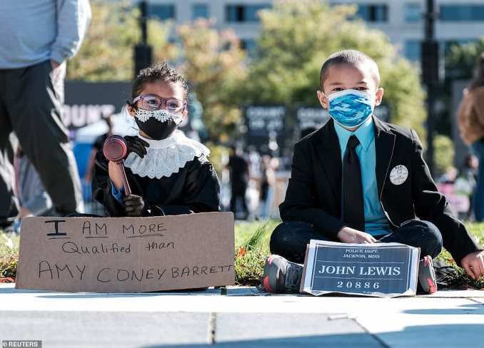 Young children dressed up as Ruth Bader Ginsburg (left) and the late House Rep. John Lewish (right) are seen above in Washington, DC, on Saturday