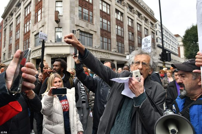 Piers Corbyn, 73, who was previously fined £10,000 for his part in a previous rally, stood with a megaphone among the crowd that had gathered in Oxford Street earlier today