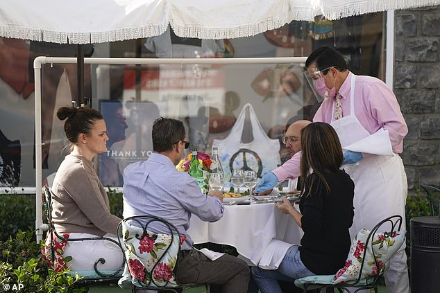 Under the new order non-essential businesses such as restaurants will have to close at 10pm. Pictured: Diners are served at a restaurant in Hollywood on Wednesday