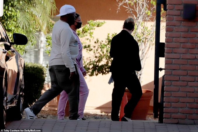 Brown was led to the guard booth at his gated community and appeared to be shown CCTV footage by LAPD detectives who had arrived at the scene earlier