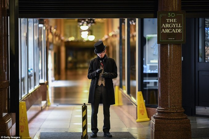 A member of staff waits to close the Argyll Arcade as the Level Four rules came into force in Glasgow tonight