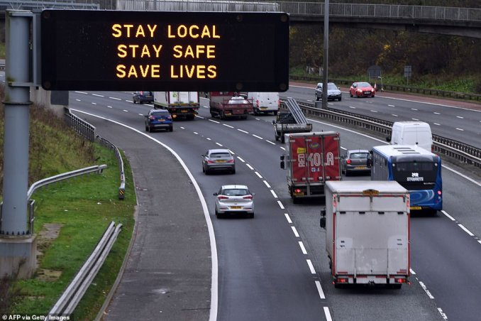 Cars pass a coronavirus warning sign on the eastbound M8 motorway in Glasgow today