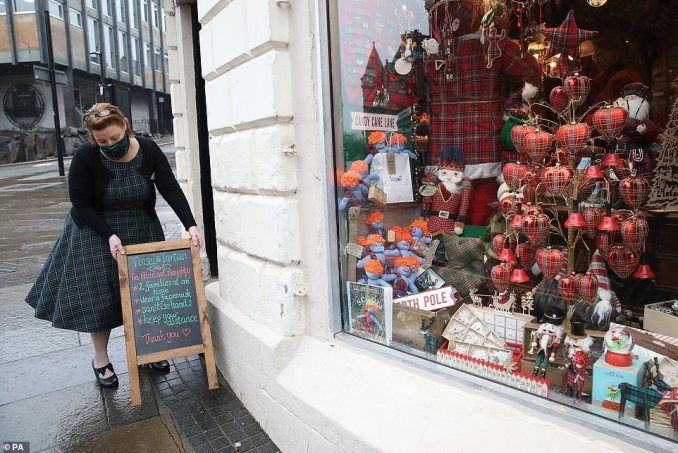 Lyndsey McDermott moves a notice board describing social distance measures at her Christmas Shop, Tinsel & Tartan, in Stirling today. The shop will close today due to latest restrictions with her online business to continue