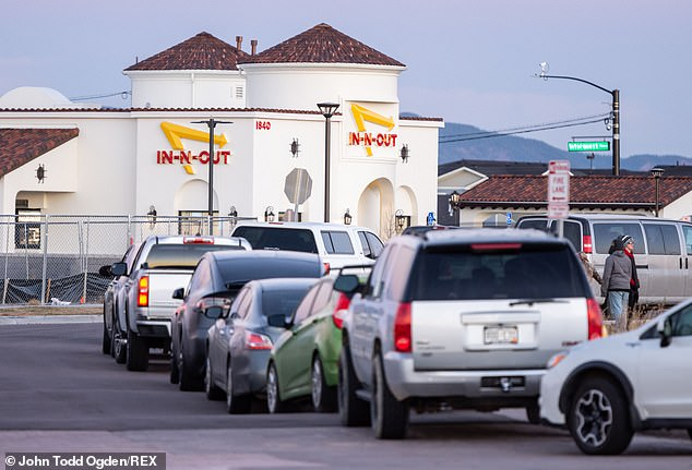 Customers are seen waiting in long car lines on Friday morning, waiting to get into the Colorado Springs In-N-Out location