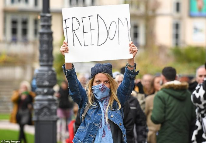 An activist holds up a sign saying 'freedom' during the anti-lockdown march in the seaside town of Bournemouth this afternoon
