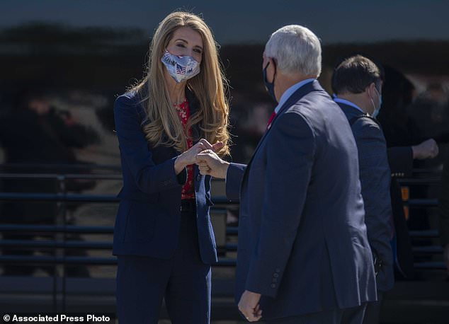 Loeffler greets Pence with a fist-bump as he arrives at Dobbins Air Reserve Base on Friday