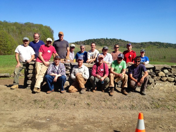 Dry stone wall workshop participants and instructors with completed portion of wall