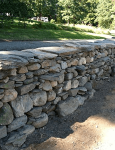 Completed section of dry stone wall built in a workshop.