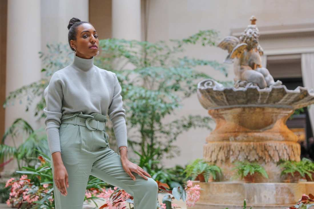 Lana Jackson stands in front of marble fountain with green plants wearing pistachio trend outfit and snakeskin print heels
