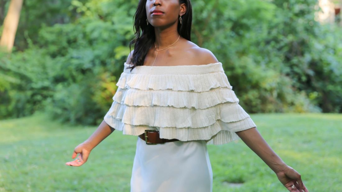 Lana Jackson surrounded by summer foliage modeling MANGO ruffled off shoulder top
