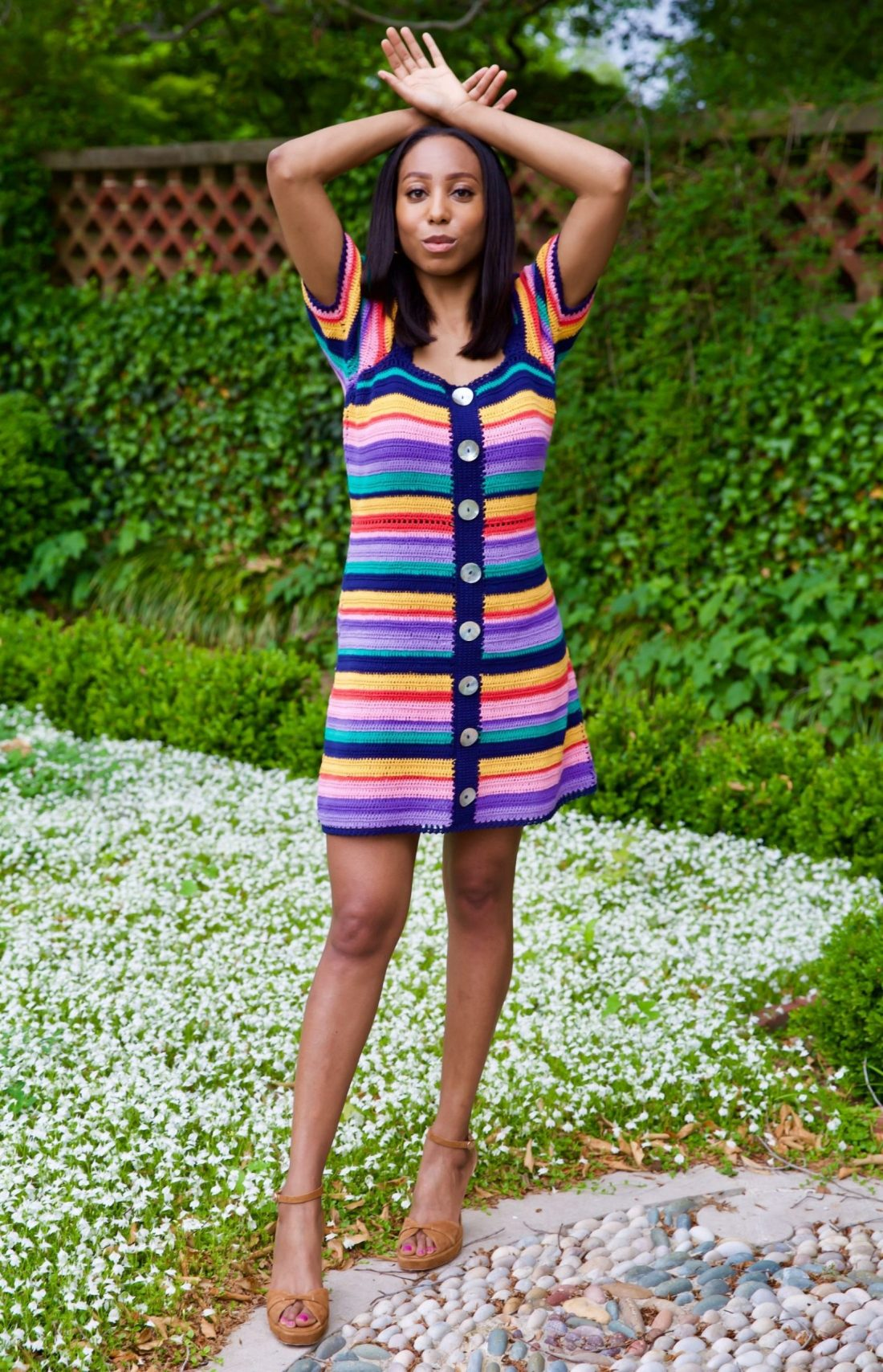 Jilene Jackson stands posing with arms above and rested on her head wearing Farm Rio Rainbow Crochet Mini Dress