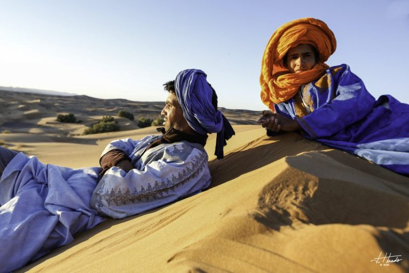 Two Amazigh (Berber) men rest on a sand dune in the desert.