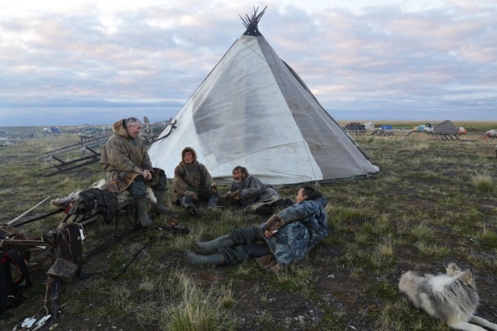 "Native American history: Nomadic people in modern Siberia, next to a house they call a ""chum."""