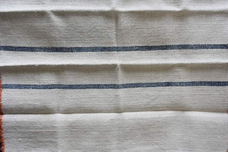 A handwoven dishtowel made out of a flour sack.