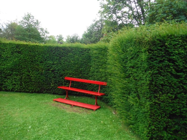 red park bench against a tall hedge. Stress relief on the go.