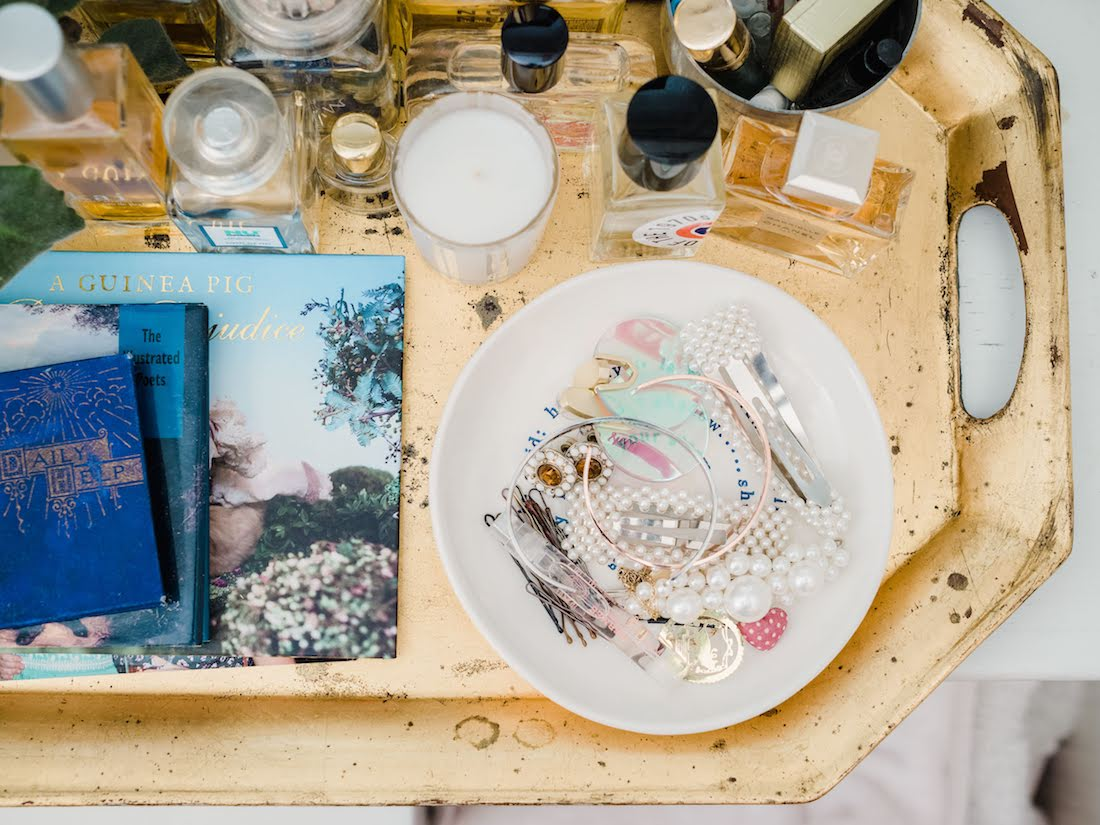 tray with books, perfumes and hair accessories