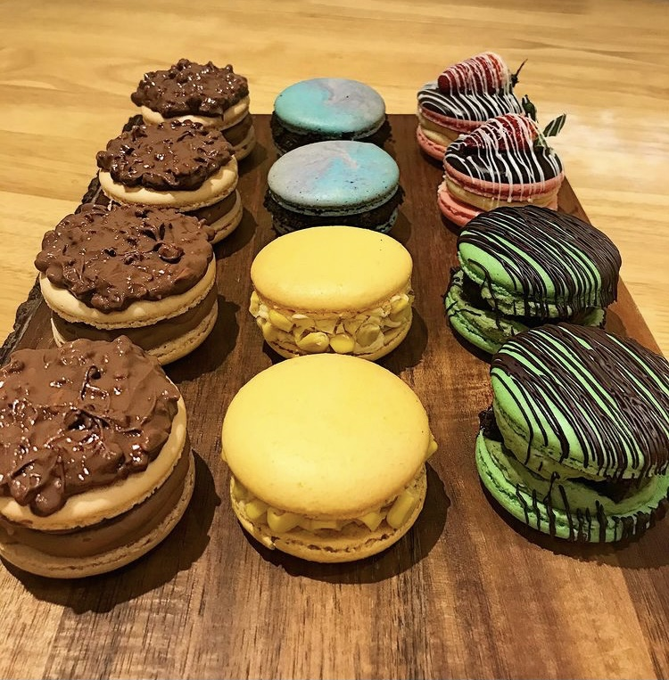 In this image, a variety of macarons that Arisa has made are on display. Four of them on the left are covered in chocolate on the top and the macaron is a beige colour. Another two in the middle are yellow with a yellow icing filling. The other two in the middle are a swirl of purple and blue. On the right, two of the macarons are green and have chocolate drizzled on top. The last two are pink, have a strawberry on top and chocolate on top.