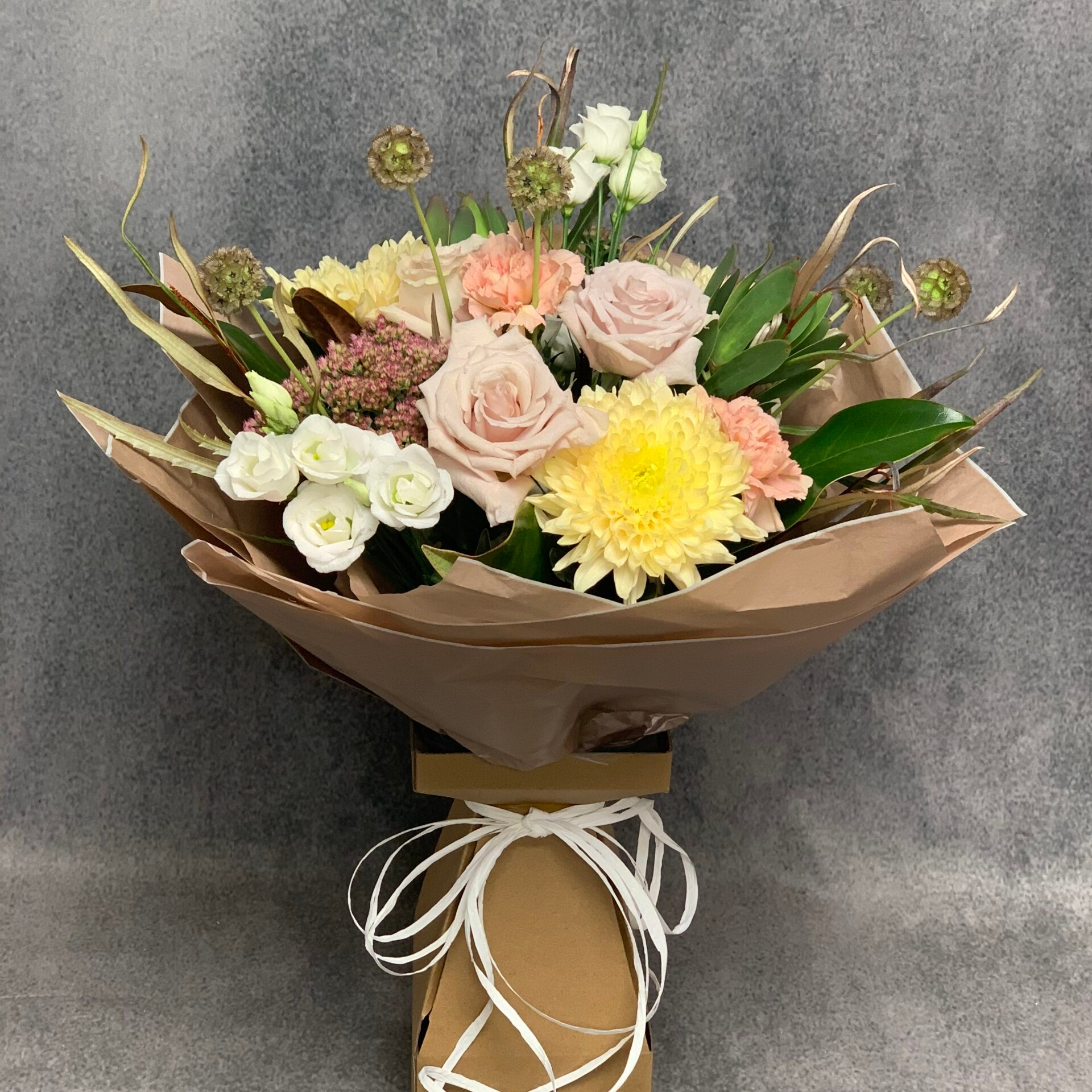 In this image, Willow's 'Bonnie Traditional Bouquet' is against a grey background. The bouquet has a mixture of yellow, white and pink flowers.
