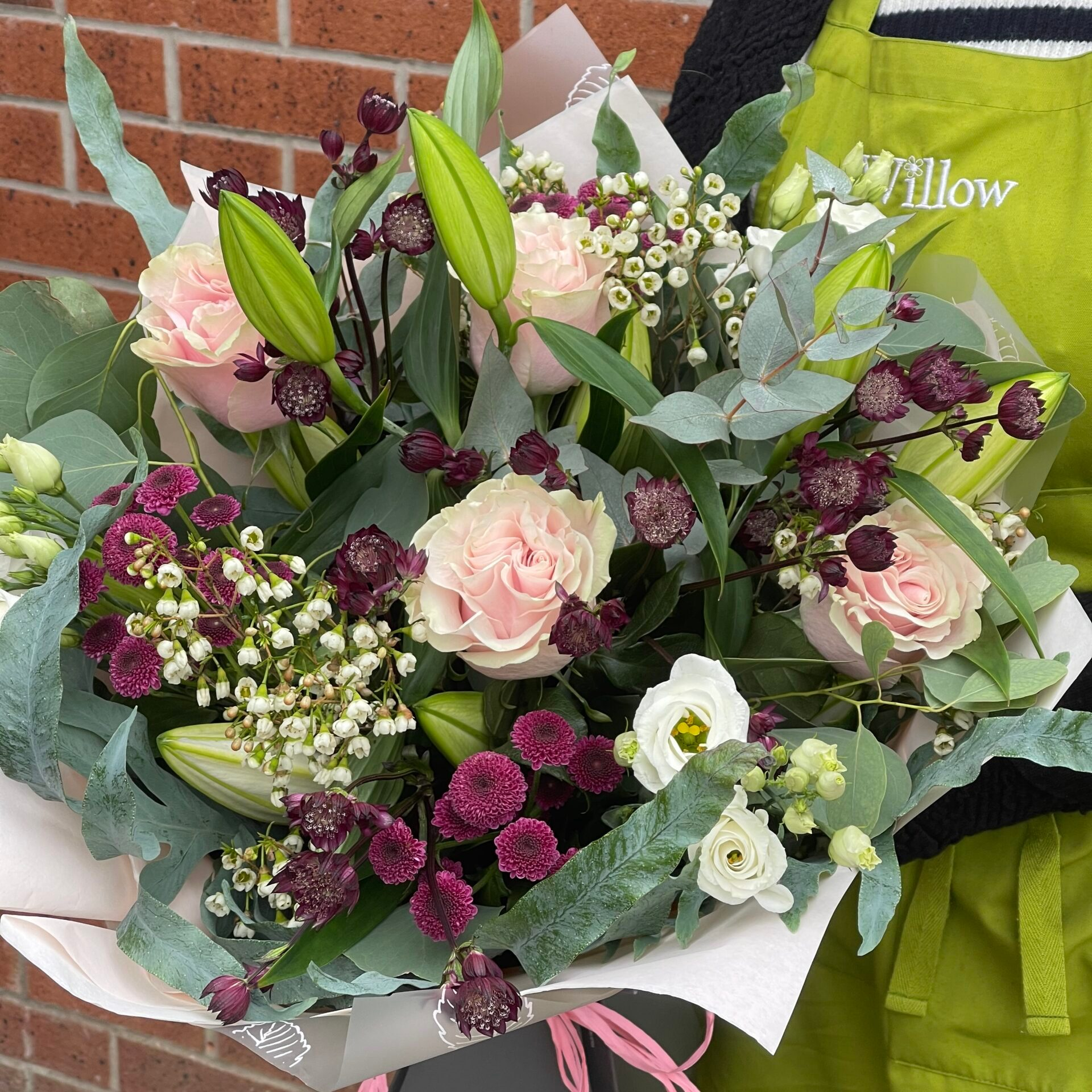 In this image, someone is wearing a green apron and is holding what they call their 'Vintage Bouquet'. This consists of light pink, white, deep purple flowers with some green foliage.