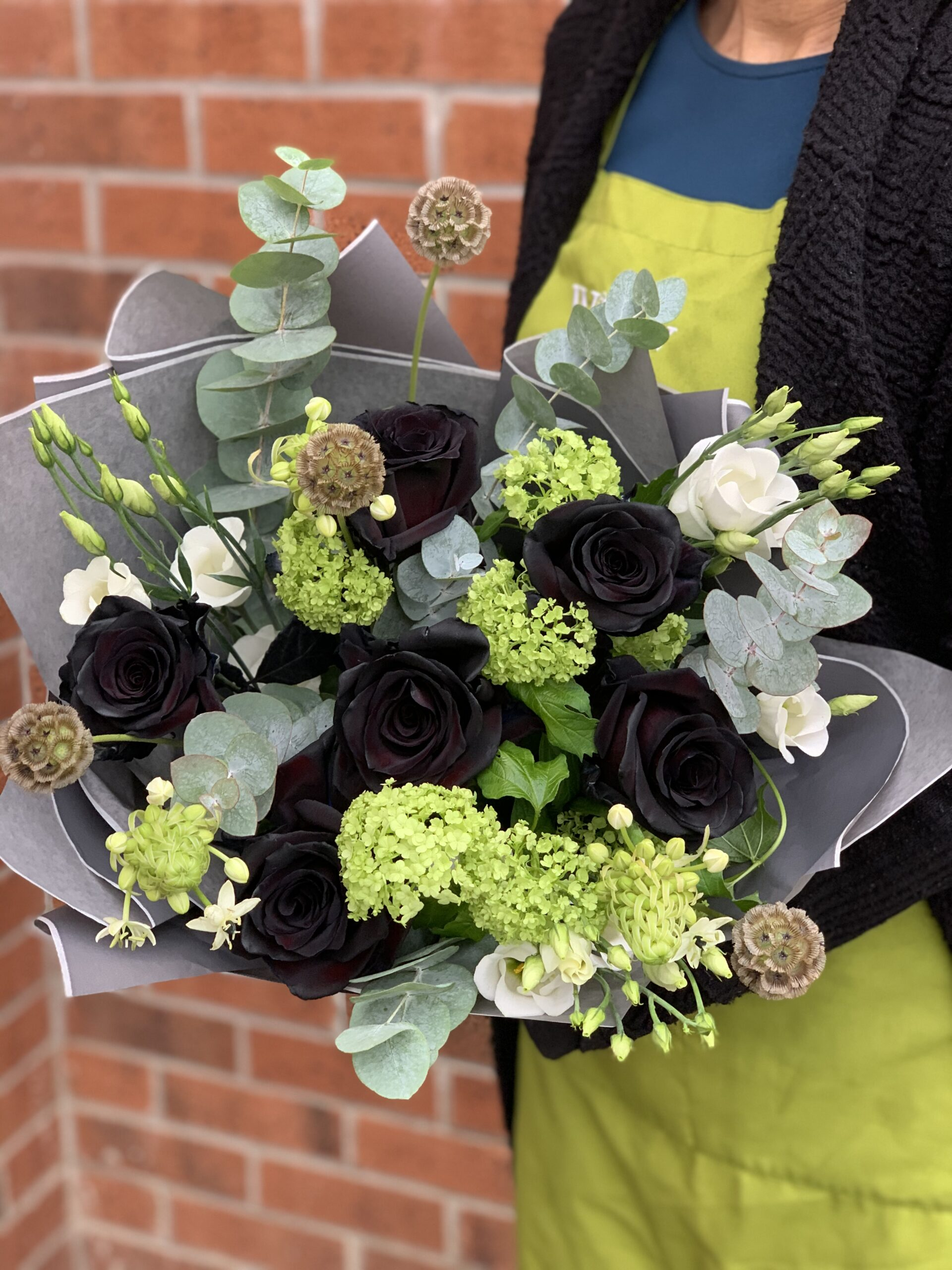 In this image, someone wearing a green apron is holding a bouquet of black flowers.