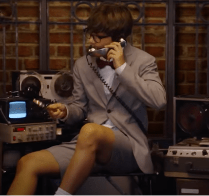 In this image, V from BTS is wearing a grey suit and the trousers are actually shorts. he is pretending to be a spy for their Dope music video.