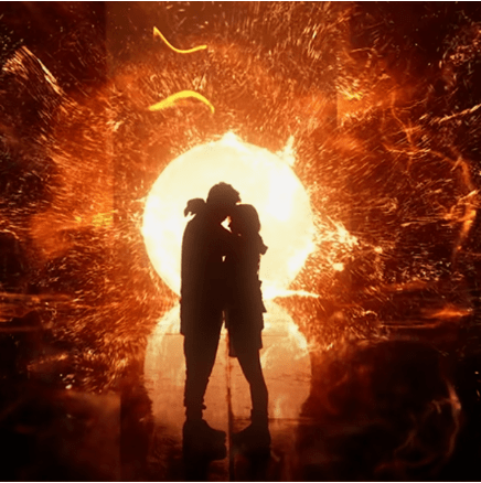 In this image, two people are facing each other closely. Behind them is an orb of glowing yellow light.