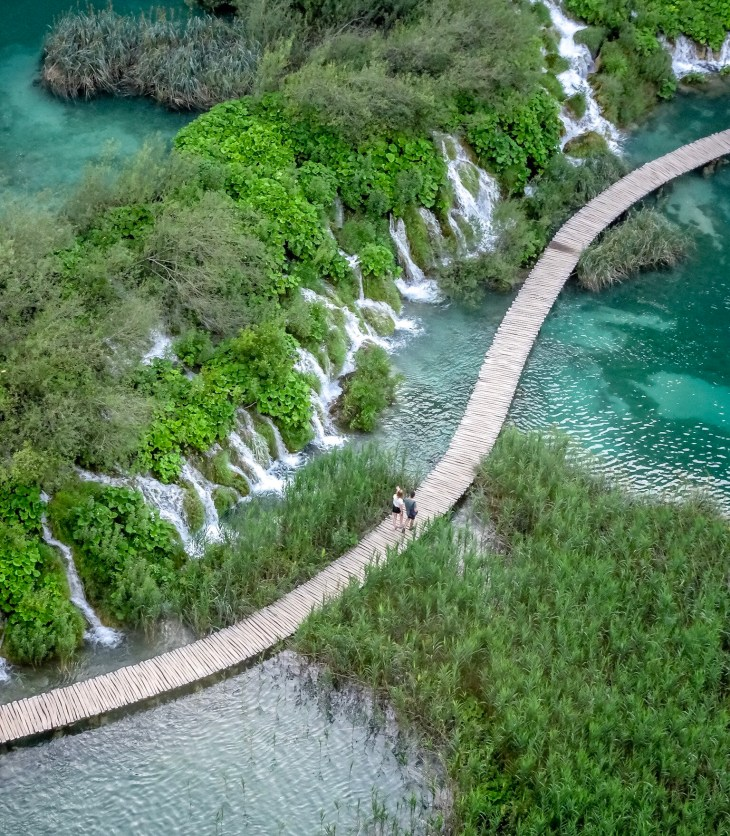 Aerial view of wooden path over a lake, next to a waterfall.