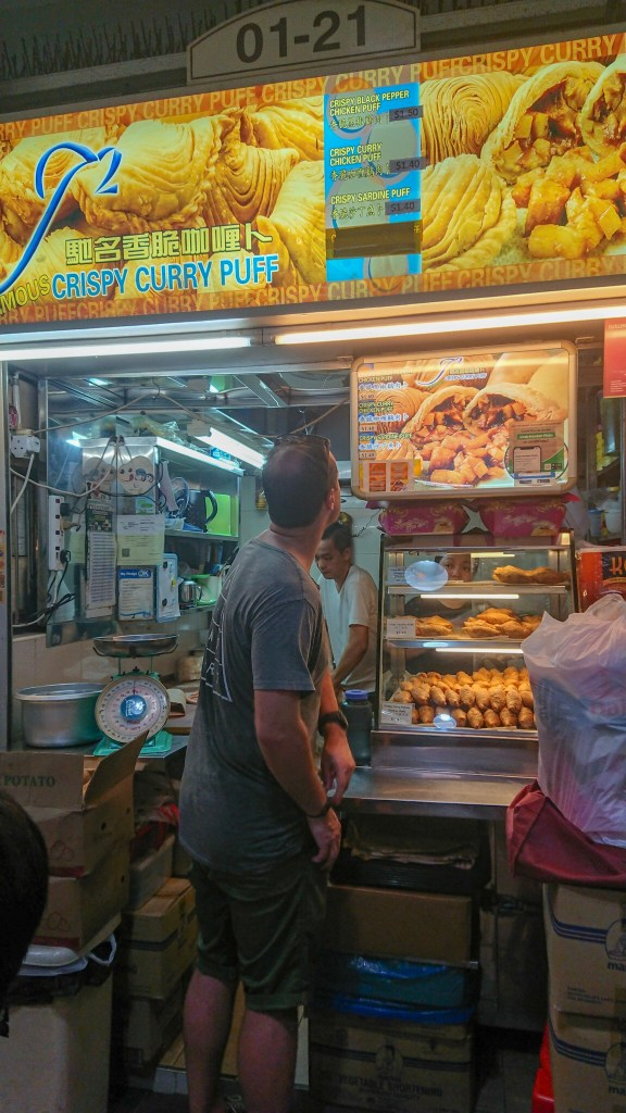 Myles purchasing curry puffs at J2 famous crispy curry puff stand in Singapore