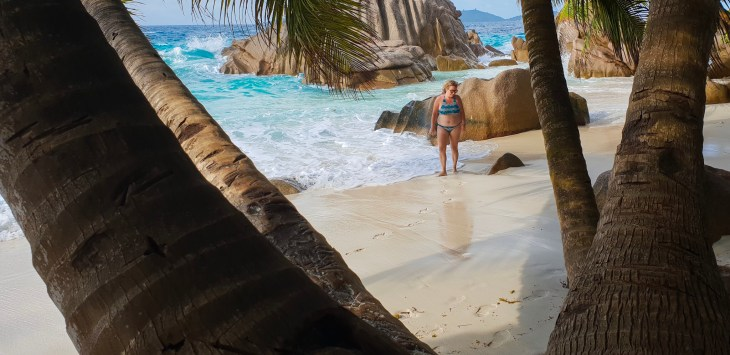 Keelie standing on beach framed by palm tree trunks.