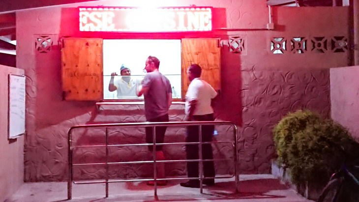 One man ordering food from a server from a small window, one man waiting in line.