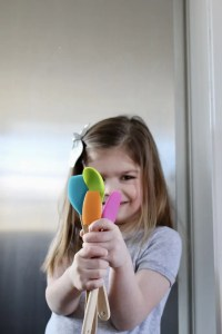 Young girl holding colorful spatulas_Emily Schiller RDN
