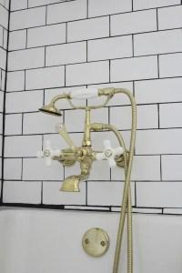 shiny gold bath faucet white subway tile