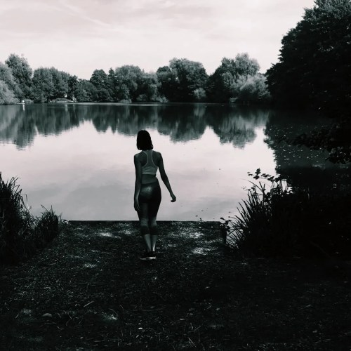 Black and white image of girl by river.