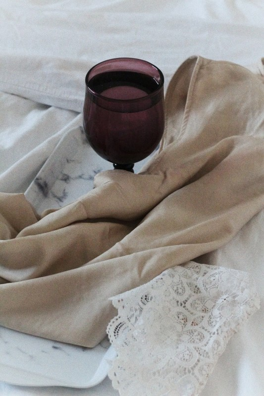 Purple wine glass with silk top on white bed