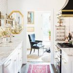 white kitchen, colorful rug, brass hardware