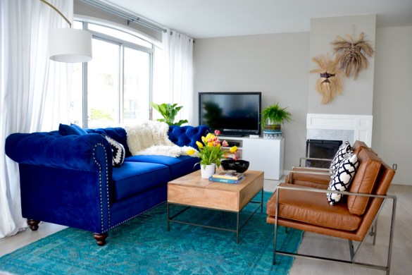 Navy blue velvet chesterfield sofa, cognac leather west elm accent chair, teal vintage persian rug, farrow and ball per beck stone grey walls // thestylesafari.com