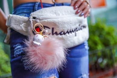 kasey ma of the stylewright champion belt bag with a smoko elodi unicorn keychain for new york fashion week 2019