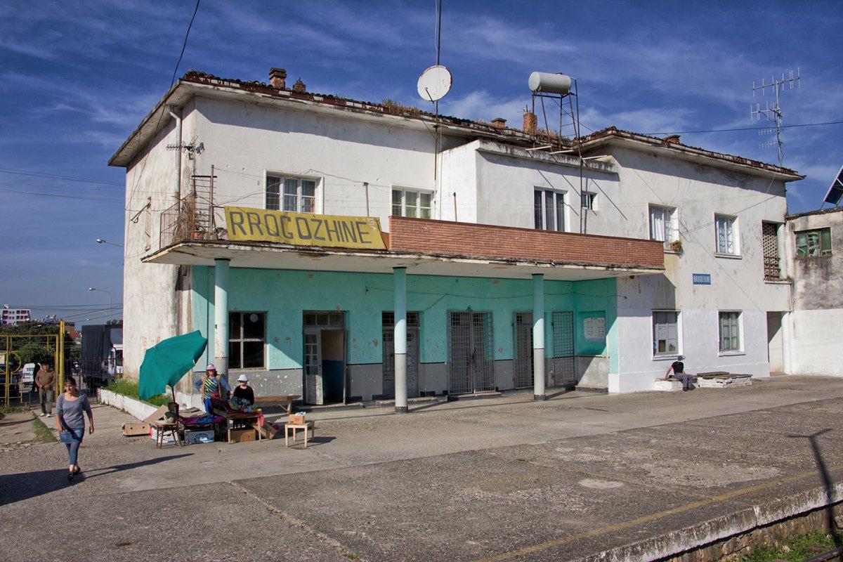 Sui marciapiedi della stazione di Rrogozhine, la capostazione allestisce una bancarella per arrotondare uno stipendio non certo milionario.