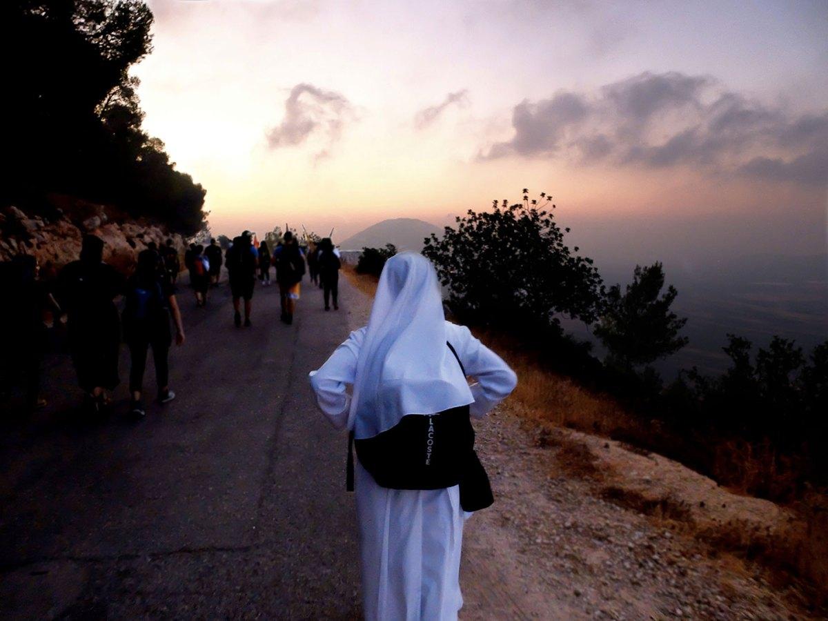 Una suora guarda l'orizzonte all'alba durante la Marcia Francescana lungo il cammino verso il Monte Tabor
