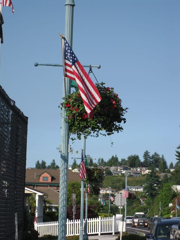 "Flags and flower baskets decorate Lafayette street in Steilacoom in advance of the summer season: Farmers Market begins June 11; concerts begin June 25. Come visit the ""Town on the Sound."""