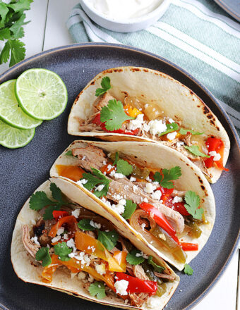 three pork tacos on a gray plate with limes and sour cream in a bowl.