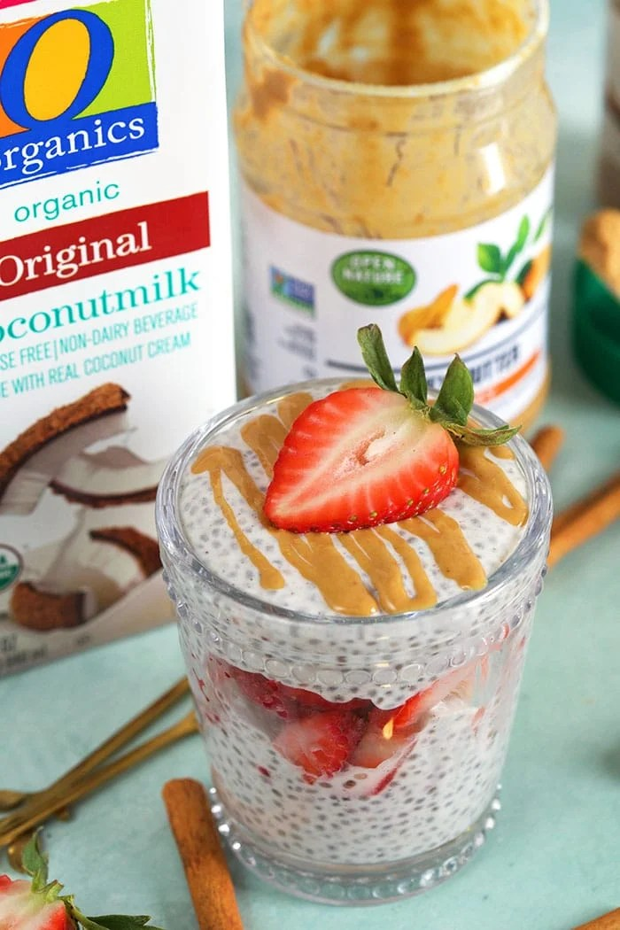 chia pudding layered in a glass with strawberries on a blue background with cashew butter in the background.
