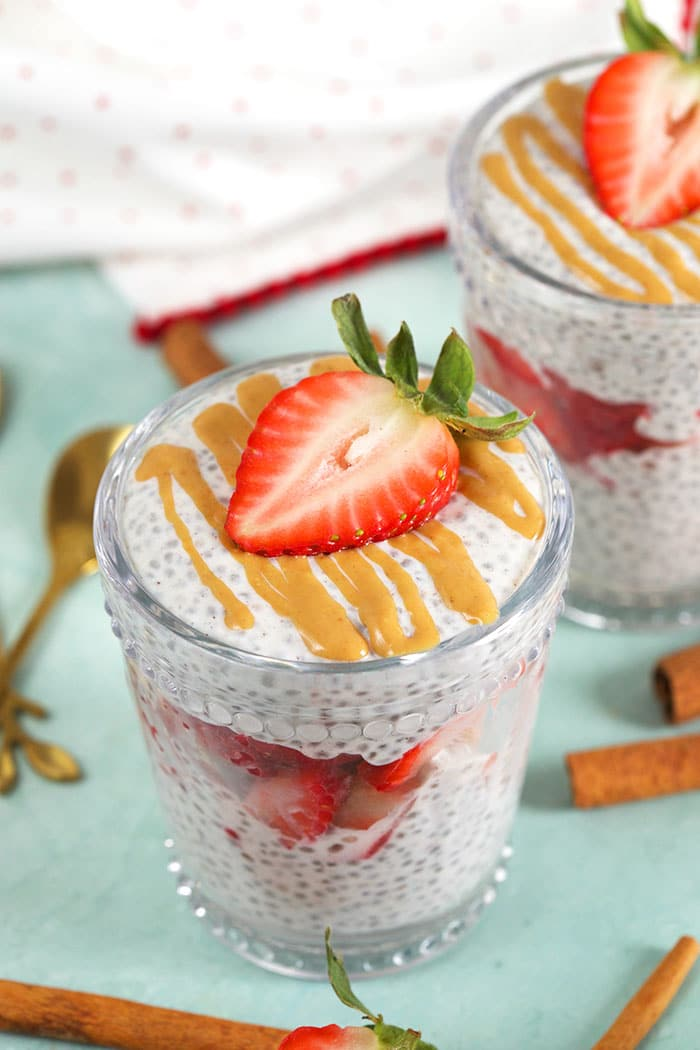 chia pudding in a glass with cinnamon sticks around it.