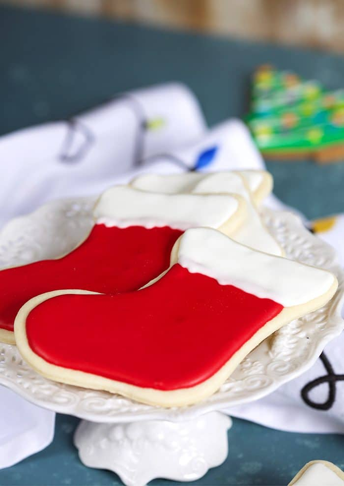 Two red stocking cookies on a white cake plate.