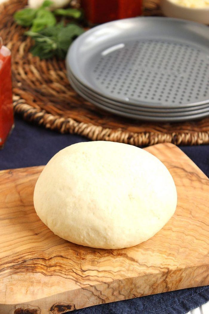 homemade pizza dough on an olive wood board with small pizza pans in the background.   The Suburban Soapbox