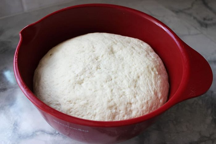 pizza dough rising in a red bowl