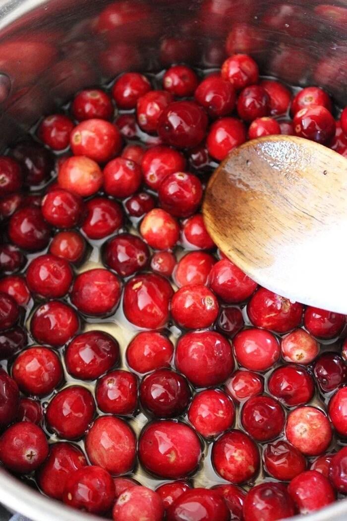 Cranberries in a saucepan in a sugar syrup bath.