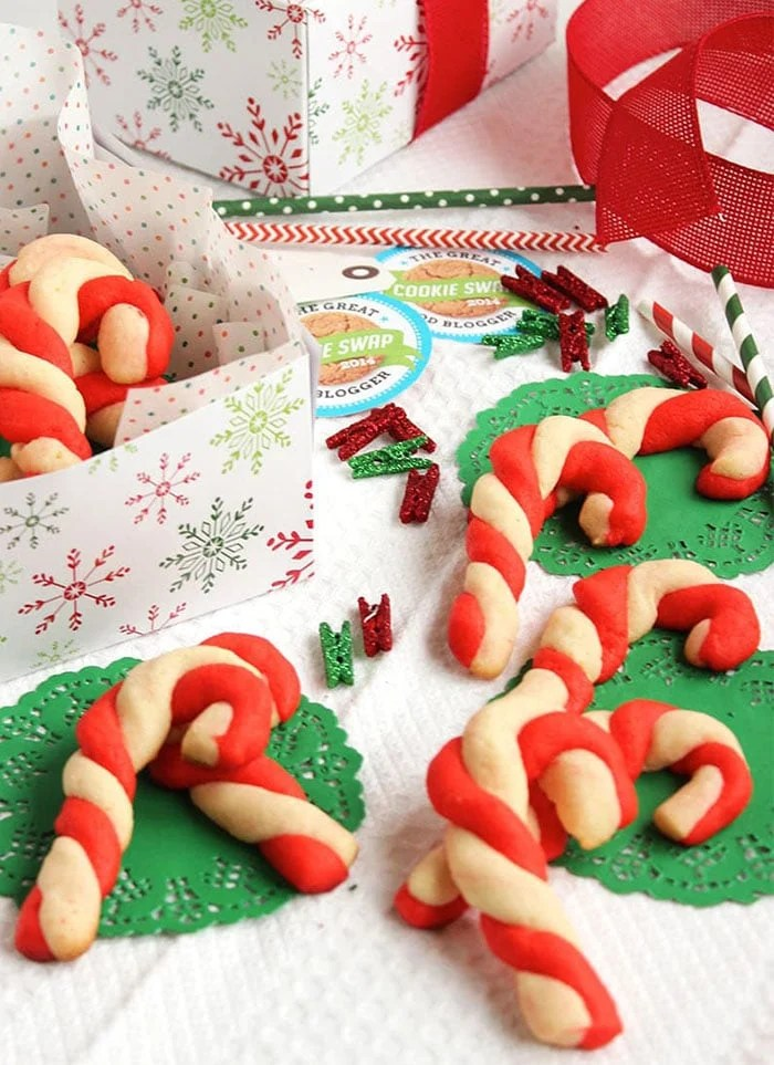 Candy cane shortbread cookies on a white background with a box of cookies in the background.